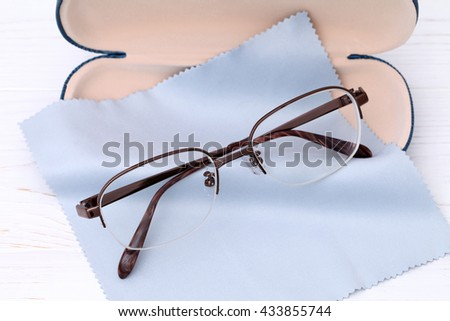 Glasses and case with glasses cleaning cloth on white wooden table  - stock photo