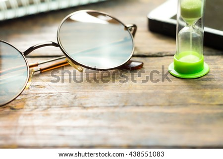 Glasses and hourglass on a wooden floor