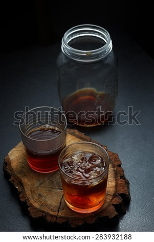 Glasses and jar of filter coffee on a wooden board. Toned image.