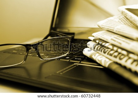 Glasses and laptop in composition sepia toned