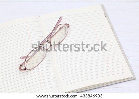 Glasses and note book on the white wooden table