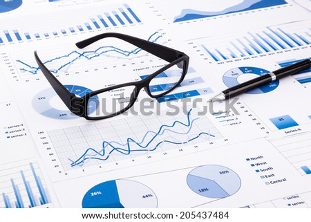 glasses and pen on blue charts, graphs, data and document background for financial and business concepts - stock photo