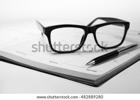 Glasses and pen on business graph chart paper with calendar.For business and financial concept ideas background.