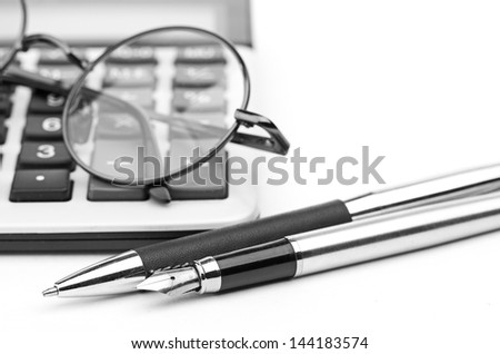 glasses and pen on calculator