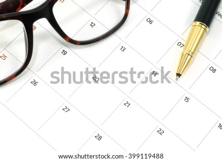 glasses and pen on calender date in business concept
