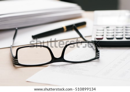 Glasses and pen on desk