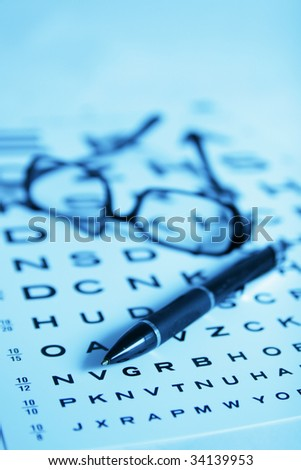Glasses and pen on eye chart - stock photo