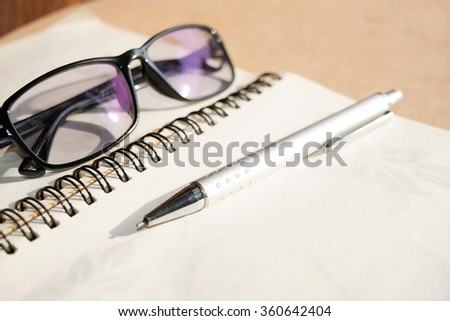 Glasses and pen on notebook - Soft light style - stock photo