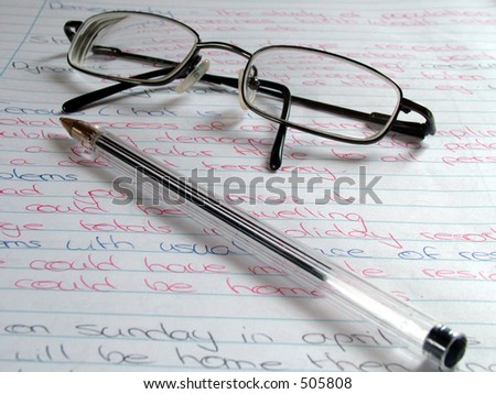 Glasses and pen on notepaper