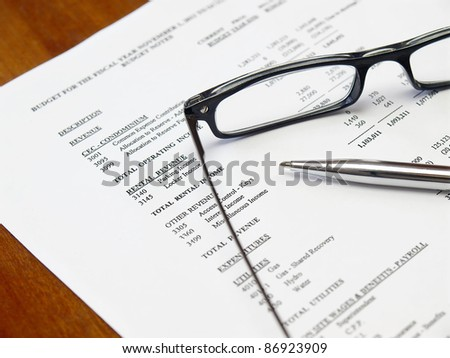 Glasses and pen on the budget document - stock photo