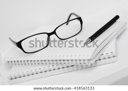 glasses and pen on white notebook in cell