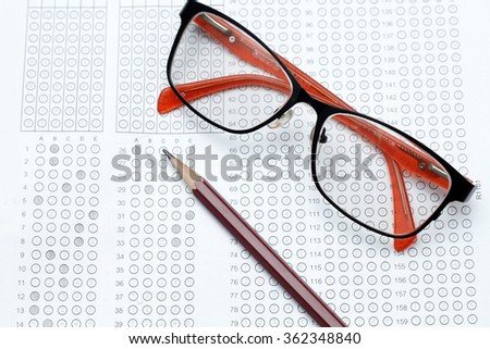 glasses and pencil on Standardized test form with answers bubbled in and a pencil, focus on answer sheet - stock photo