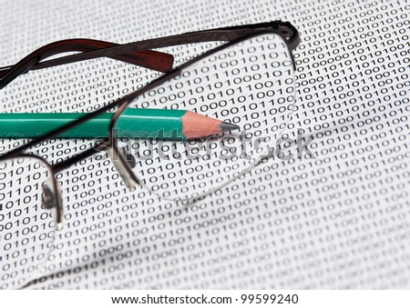 glasses and  pencil on the background of a binary code