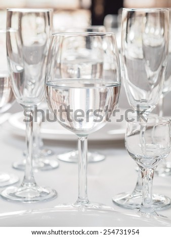 Glasses and plates on table in restaurant - stock photo