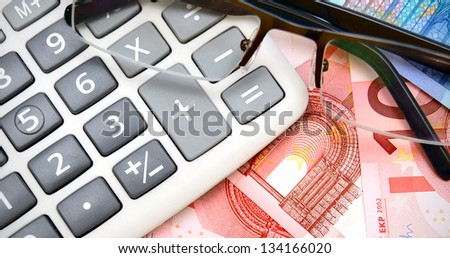 Glasses and the calculator for euro. - stock photo