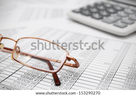 Glasses and the calculator on documents. - stock photo
