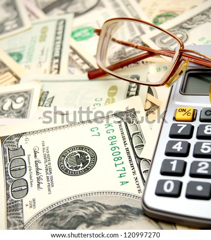 Glasses and the calculator on dollars. - stock photo