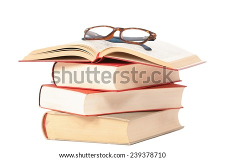 Glasses are laying on a isolated  book staple - stock photo