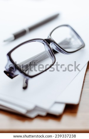 Glasses, ballpoint pen close-up on white paper for notes - stock photo