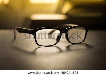 glasses black , Sunglasses On a desk by the window Light evening pass through.