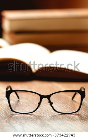 Glasses, book and cup of tea on a wooden table