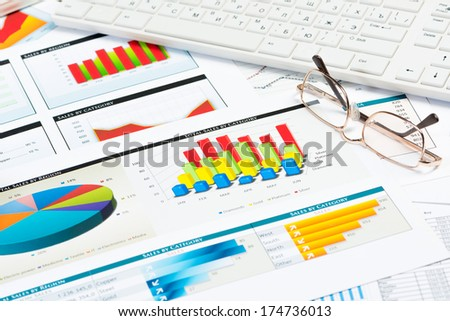 glasses, business papers with graphs and keyboard, still life