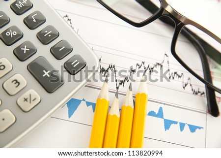 glasses, calculator, schedule, and a pencil on the desk - stock photo