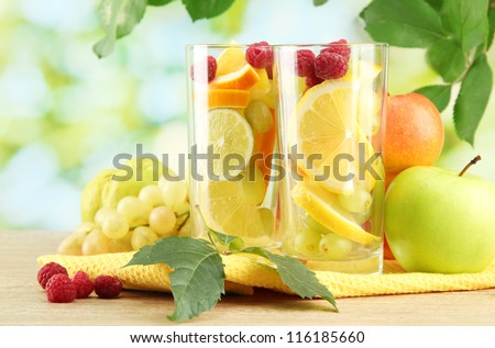 glasses citrus fruits and raspberries, on green background - stock photo