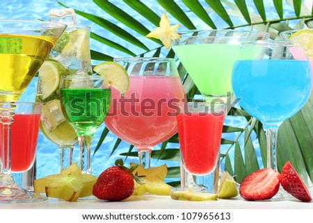 Glasses cocktails on table on blue sea background
