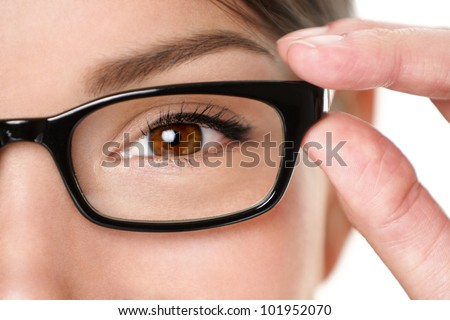 Glasses eyewear closeup of woman holding eye glasses frame smiling happy. Beautiful young mixed race Caucasian / Asian Chinese woman wearing black glasses. - stock photo