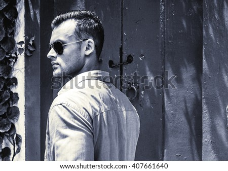 Glasses fashion beauty concept. Portrait of a young and handsome man in a white shirt and trendy glasses posing over blue wooden background. Close up. Street shot. - stock photo