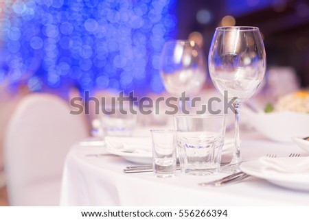 Glasses, flower fork, knife served for dinner in restaurant with cozy interior and bokeh in background