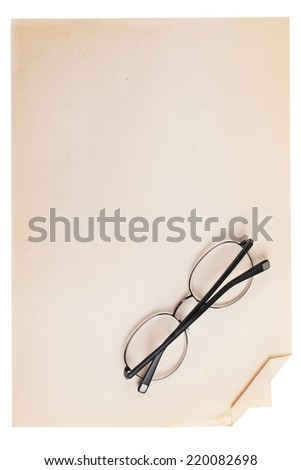 Glasses folded lie on a vintage piece of paper on a white background.