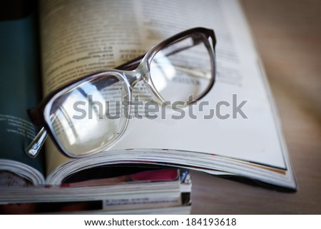 glasses for reading on a stack of magazines - stock photo