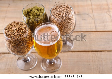 Glasses full of light beer, different types of malt and hops over a wooden background - stock photo