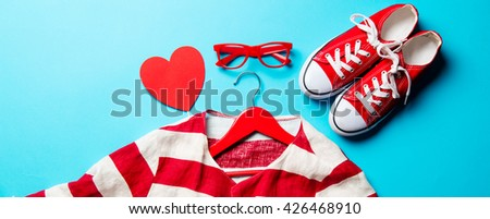glasses, heart shaped toy, gumshoes, jacket on the hanger and laptop on the blue background - stock photo