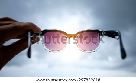 glasses in hand on sky , concept of future  - stock photo