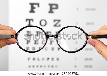 Glasses in hands on eye chart background, close-up