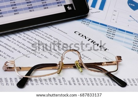 Glasses is on the front. Contract paper behind them. Marketing reports - digital and paper are on the background