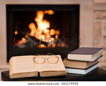 glasses lie on a book by the fireplace - stock photo