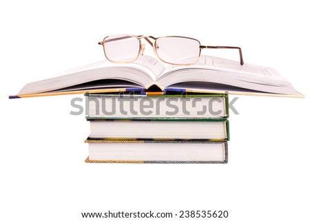 Glasses lie on a pile of books with open - stock photo