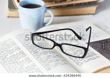 glasses lying on an open book next to the mug of coffee on background of stack of old books
