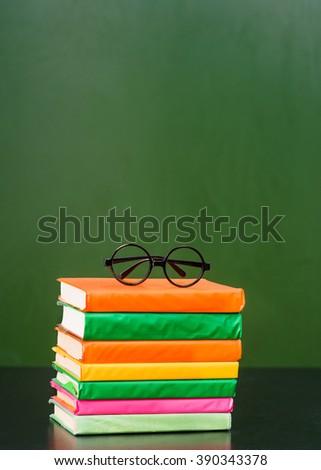 Glasses lying on the books near empty green chalkboard - stock photo
