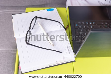 Glasses lying on the laptop table near open blank page of a diary with a pen for making appointments, organising a schedule - stock photo