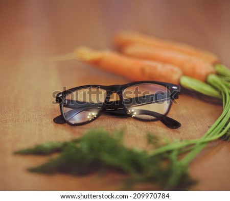 Glasses next to a carrot on the wooden background. Retro toned image