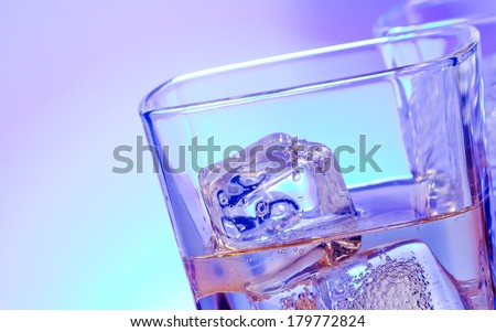 glasses of alcoholic drink cocktail with ice on disco blue light with space for text