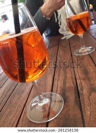 Glasses of an orange beverage with straws and ice on a wooden table, with an unrecognizable person in background - stock photo