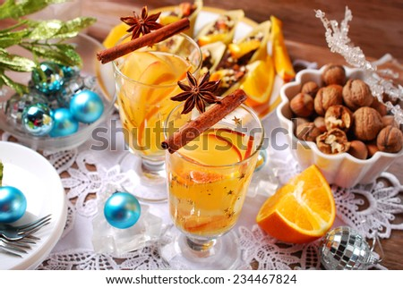 glasses of apple and orange drink with cinnamon and anise on christmas table - stock photo
