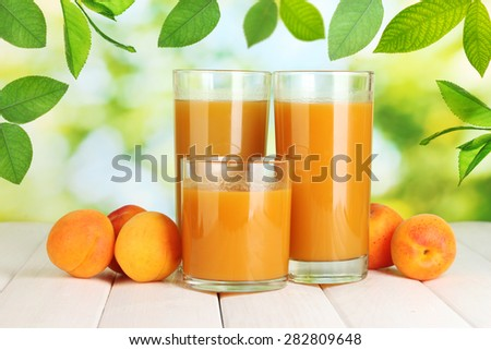 Glasses of apricot juice and fresh apricots on table on green background - stock photo