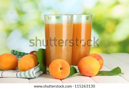 glasses of apricot juice  and fresh apricots on white wooden table on green background